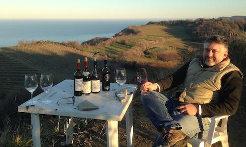 Luigi Mancini, owner of Fattoria Mancini in Strada dei Colli in Pesaro, tel. +39.0721.51828, sitting in Rive Alte, his most panoramic plot of land, overlooking the Adriatic Sea