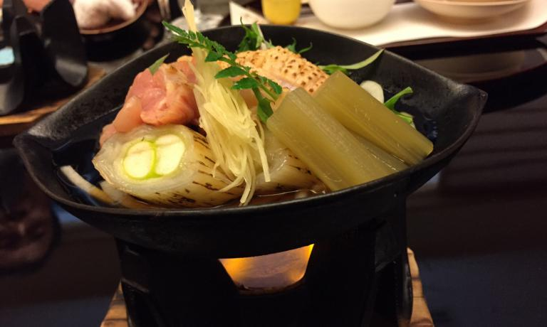 Sukiyaki (saucepan on a flame) with chicken, onion, vegetables and mirin (sweet saké)
