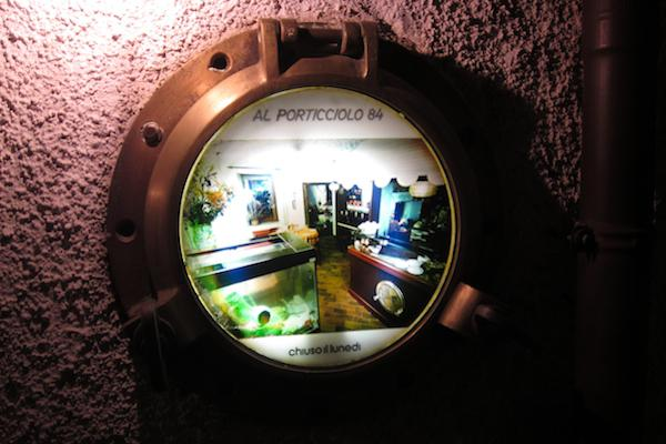 A detail of the entrance to Al Porticciolo, the restaurant opened in 1984, in Lecco, by the Ferrari family, in Via Fausto Valsecchi 5, tel. +39.0341.498103. It is because of this very date that on the porthole there's written Al Porticolo 84. Fabrizio Ferrari, born in 1980, starred chef since the 2004 edition of the Michelin Guide, has never betrayed the vocation of his parents for a seafood cuisine, except he transforms it following his ideas and experiences. The dishes that made the fortune of this restaurant during the last century are not missing. Therefore, two ways of cooking fish share the same roof