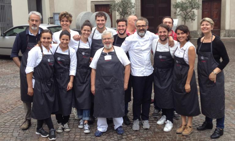 The dining room and kitchen team at work yesterday at Refettorio Ambrosianoin Piazzale Greco, in Milan, a charity project that has fine dining, art and design involved. Dressed in white, Massimo Bottura, chef at Osteria Francescana in Modena and the soul of Refettorio. To his left, Rene Redzepi, chef at Noma in Copenhagen, one of the great chefs included in the programme. Among the waiters there was also Zanatta, author of this piece, invited by Caritas