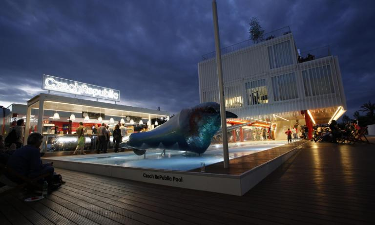 A night view of the entrance to the pavilion of the Czech Republic, with the swimming pool, the bar and the large sculpture purifying the water in the fountain