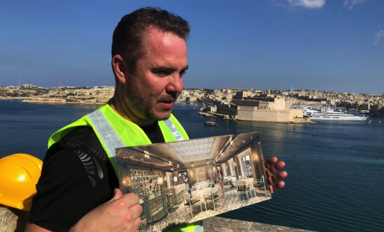 PatronMark Weingardwith renderings of the project, still a building site. Behind him, Fort Saint Angelo