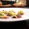 Pesto tortelli on a carpaccio of smoked beef, vineyard snails, pine nuts, sauce of ginger and olives, thyme