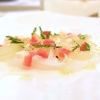 Carpaccio di scampo, maionese di pesca, limone salato, uva bianca, germogli di carote selvatiche, pomodoro cotto a bassa temperatura