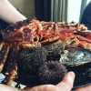 It's a dish with seafood, including a huge (and alive) king crab, sea urchins and oysters